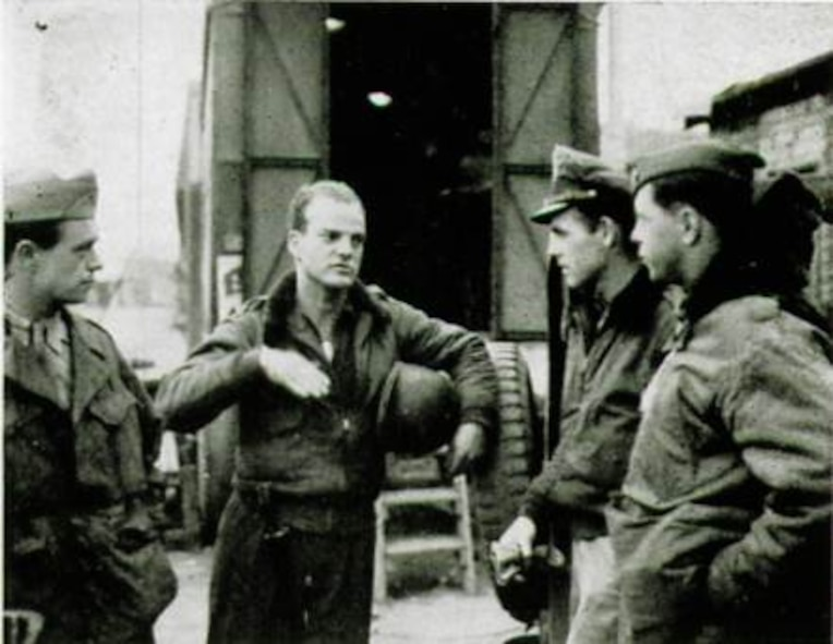 First Lieutenant Edward R. Kirkland, from Coral Gables, Florida, gesturing with hand to unidentified personnel, flew in the 406th Fighter Squadron and had an exciting story to tell after returning to the unit following his shoot down, capture and escape.  As seen here, for pilots some things are better explained by hands.  (The Story of the 371st Fighter Group in the E.T.O.)
