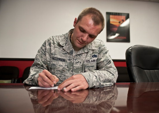 Master Sgt. Dennis Hutchison, 57th Aircraft Maintenance Squadron Tomahawks Aircraft Maintenance Unit production superintendent, fills out a pledge form for the 2015 Air Force Assistance Fund drive at Nellis Air Force Base, Nev., March 17, 2015. Hutchison's father passed away in 2005 and he did not have enough money to travel to his hometown in Missouri from his assigned duty station in Georgia, but received an interest-free loan from the Air Force Aid Society to cover his travel costs. Now an avid supporter of the AFAF, which supports and funds four different charities including the AFAS, Hutchison encourages Airmen of all ranks and ages to donate to the AFAF drive. (U.S. Air Force photo by Staff Sgt. Siuta B. Ika)