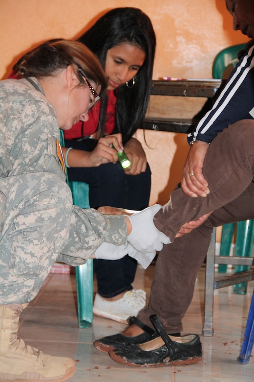 Maj. Rhonda Dyer, Joint Task Force Bravo Medical Element community health nurse, checks the foot of a Honduran local during a Medical Readiness Training Exercise, March 11-15, 2015. Joint Task Force-Bravo's Medical Element (MEDEL), with support from JTF-Bravo's Joint Security Forces and Army Forces Battalion, partnered with the Honduran Ministry of Health and the Honduran military to provide medical care to more than 5,352 people and performed 11 surgeries over three days in the Department of Copan and Lempira, Honduras during a Mobile Surgical Team (MST), Medical Readiness Training Exercise (MEDRETE), and a Medical Partnership Exercise (MPE). (Photo by U.S. Army Sgt. Stephanie Tucker)