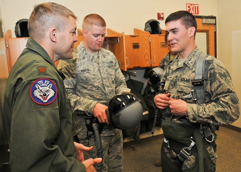 Maj. Karl Palmberg, 175th Fighter Squadron pilot, explains how to don a flight suit before a takeoff to Cadet 3rd Class Cole Jorgensen, South Dakota State University ROTC student, at Joe Foss Field, March 19, 2015. Jorgenson, a sophomore at SDSU, and more than 30 fellow cadets toured the 114th Fighter Wing and were briefed about the many roles and specialized fields that make up the South Dakota Air National Guard.(National Guard photo by Staff Sgt. Luke Olson/Released)