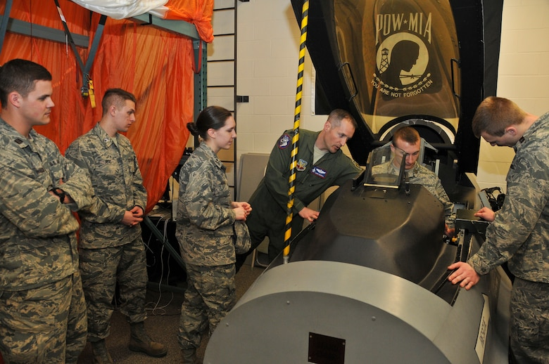 Lt. Col. Mark Morrell, 114th Operations Support Squadron commander, explains the controls of the pilot ejection (egress) trainer on the F-16 to the South Dakota State University ROTC cadets at Joe Foss Field, S.D., March 19, 2015. The students toured the 114th Fighter Wing and were briefed about the many roles and specialized fields that make up the South Dakota Air National Guard.(National Guard photo by Staff Sgt. Luke Olson/Released)