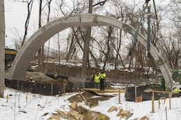 ARLINGTON, Va. – A second concrete arch is placed into position at the Arlington National Cemetery Millennium Project here March 3, 2015. The archways will support the loop road bridge, which spans a restored stream at the cemetery's 27-acre expansion project. The project will add nearly 30,000 burial and niche spaces with a mix of above-ground columbariums and in-ground burials. (U.S. Army photo/Patrick Bloodgood)