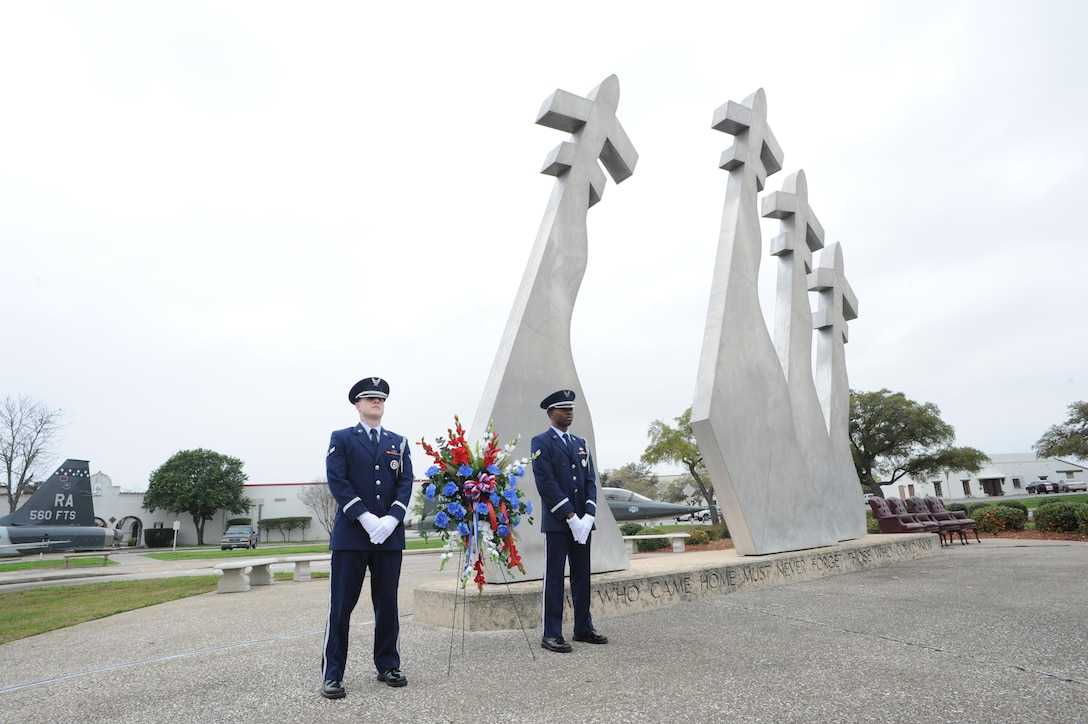 Airman 1st Class Hayden Tondee (left) and Senior Airman Willie Muhammad (right), Joint Base San Antonio Honor Guard members, stand at the Missing Man Memorial before the wreath laying ceremony, which was held in conjunction with the 42nd Freedom Flyer Reunion March 20 at JBSA-Randolph. (U.S. Air Photo by Melissa Peterson)