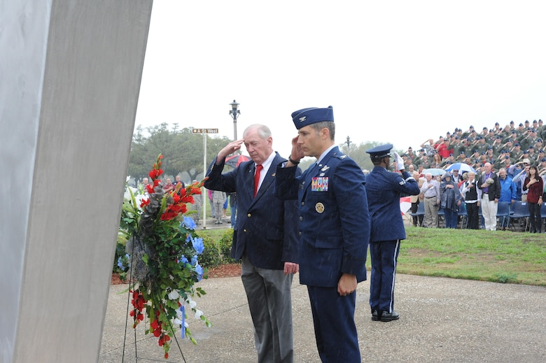 Col. Matthew Isler, 12th Flying Training Wing commander, (right) and retired Marine Lt. Col. Orson Swindle (left), whose F-8E aircraft was shot down over North Vietnam Nov. 11, 1966, salute the wreath at the Joint Base San Antonio-Randolph Missing Man Monument during a wreath laying ceremony March 20 to honor prisoners of war and those missing in action. (U.S. Air Photo by Melissa Peterson)