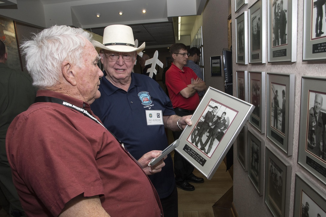 Retired Air Force Lt. Col. Thomas Collins (left), former Vietnam War POW, and retired Air Force Col. Elmo Baker, former Vietnam War POW, view Collins' Freedom Flight photo during the 560th Flying Training Squadron Artifact Dedication ceremony and open house March 20 at Joint Base San Antonio-Randolph. The annual event, in conjunction with the 42nd Freedom Flyer Reunion and 18th Annual POW/MIA Symposium, honors all POWs held captive during the Vietnam War. The tradition began when members of the 560th Flying Training Squadron were given the task to retrain more than 150 POWs returning to flying status. Collins aircraft was shot down during a mission over North Vietnam Oct. 18, 1965, and was held captive by the North Vietnamese until his release Feb. 12, 1973. Baker's aircraft was shot down during a mission over North Vietnam Aug. 23, 1967, and was held captive by the North Vietnamese until his release March 1973. (U.S. Air Force Photo by Johnny Saldivar)