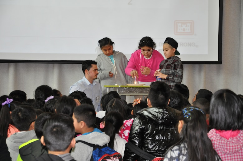 Erwin Galloza, mechanical engineer, U.S. Army Corps of Engineers, New York District performs a science experiment with three student volunteers.
