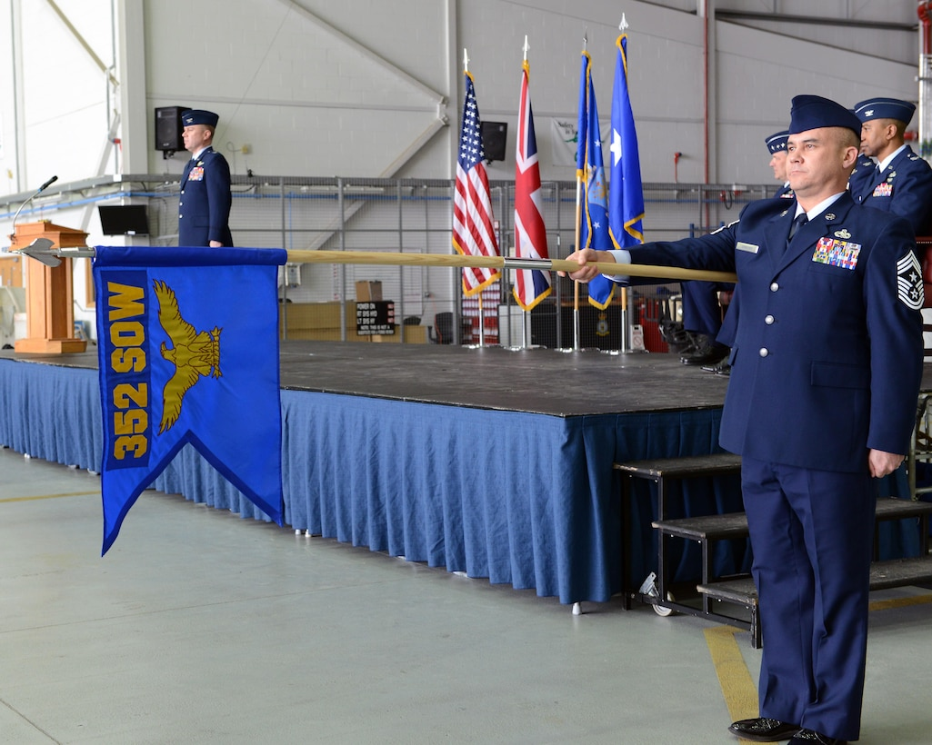 U.S. Air Force Chief Master Sgt. Robert Gibbons II presents the 352nd Special Operations Wing guideon during the 352nd SOW redesignation ceremony March 23, 2015, held in Hangar 814 on RAF Mildenhall, England. During the ceremony, the 752nd Special Operations Group and the (U.S Air Force photo by Tech. Sgt. Stacia Zachary/Released)