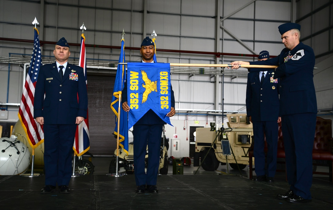 U.S. Air Force Col. Eric Faison, 352nd Special Operations Maintenance Group commander, poses after unravelling the 352nd SOMXG flag during the 352nd Special Operations Wing activation ceremony March 23, 2015, on RAF Mildenhall, England. (U.S. Air Force photo by Senior Airman Christine Griffiths)