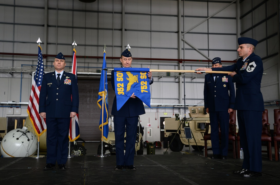 U.S. Air Force Col. Nathan Green, center, 752nd Special Operations Group commander, unravels the 752nd SOG flag during the 352nd Special Operations Wing activation ceremony, March 23, 2015, on RAF Mildenhall, England. (U.S. Air Force photo by Senior Airman Christine Griffiths)