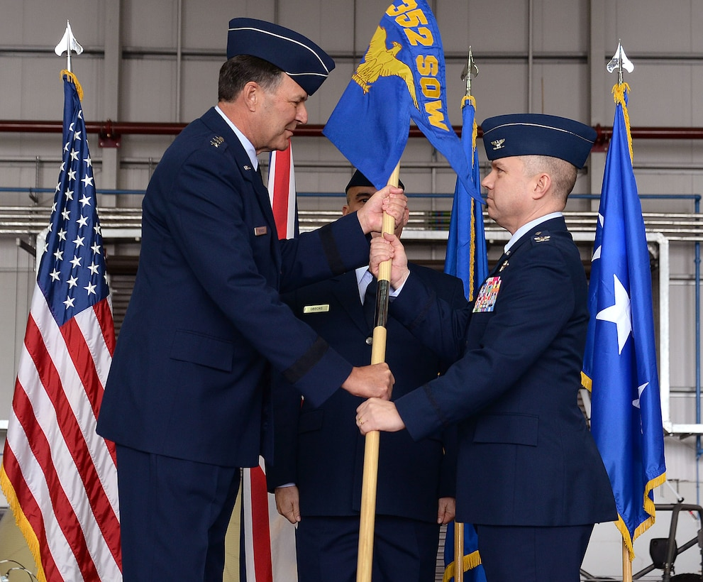 U.S. Air Force Lt. Gen. Brad A. Heithold, left, Air Force Special Operations Command commander, passes the 352nd Special Operations Wing guidon to U.S. Air Force Col. William Holt, 352nd SOW commander, during the 352nd SOW activation ceremony, March 23, 2015, on RAF Mildenhall, England. The 352nd SOW is responsible for planning and executing specialized and contingency operations using advanced aircraft, tactics and air refueling techniques to infiltrate, exfiltrate and resupply special operations forces.  (U.S. Air Force photo by Senior Airman Christine Griffiths)