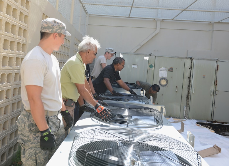 36th Civil Engineer Squadron heating, ventilation and air conditioning technicians work together to move a condensing unit for installation March 12, 2015, at Andersen Air Force Base, Guam. The mission of the HVAC Flight is to install, maintain, and repair different systems on base. (U.S. Air Force photo by Airman 1st Class Arielle Vasquez/Released)