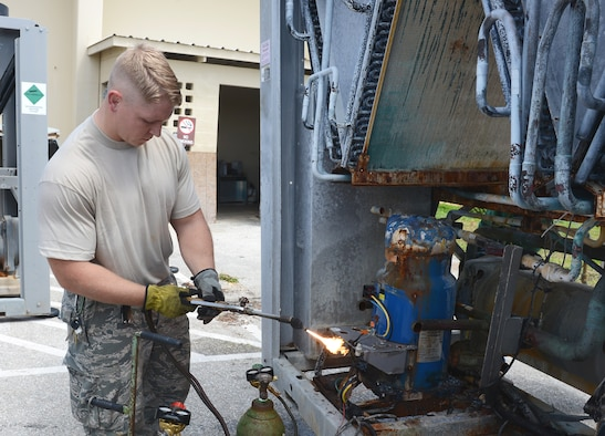 Staff Sgt. Ricky Kranning, 36th Civil Engineer Squadron heating, ventilation and air conditioning technician, uses a cutting torch to cut compressors out of a unit March 11, 2015, at Andersen Air Force Base, Guam. The mission of the HVAC Flight is to install, maintain, and repair different systems on base. (U.S. Air Force photo by Airman 1st Class Arielle Vasquez/Released)