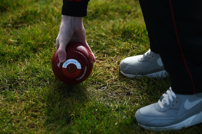 Nick Brett, 423rd Civil Engineer Squadron water and fuels shop chief, picks up a bowl from the athletic field at RAF Alconbury, England, March 23, 2015. Brett, who has played Bowls for more than 28 years, recently won the title of world champion indoor bowler. (U.S. Air Force photo by Staff Sgt. Jarad A. Denton/Released)