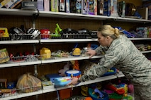 Senior Master Sgt. Shannon Last adds toys to shelves at the Chief Master Sgt. Gene R. Collins Airman's Attic at Scott Air Force Base, Illinois on March 12, 2015. Scott's Airman's Attic is manned 100 percent by volunteers, who accept and sort donations, shelve them, and assist customers. The Airman's Attic is open to military members E-4 and below and their direct dependents. All ranks can get books and uniforms. Last is the Mission Support Cell Manager at the 618th Air Operations Center. (U.S. Air Force photo by Senior Airman Sarah Hall-Kirchner/Released)