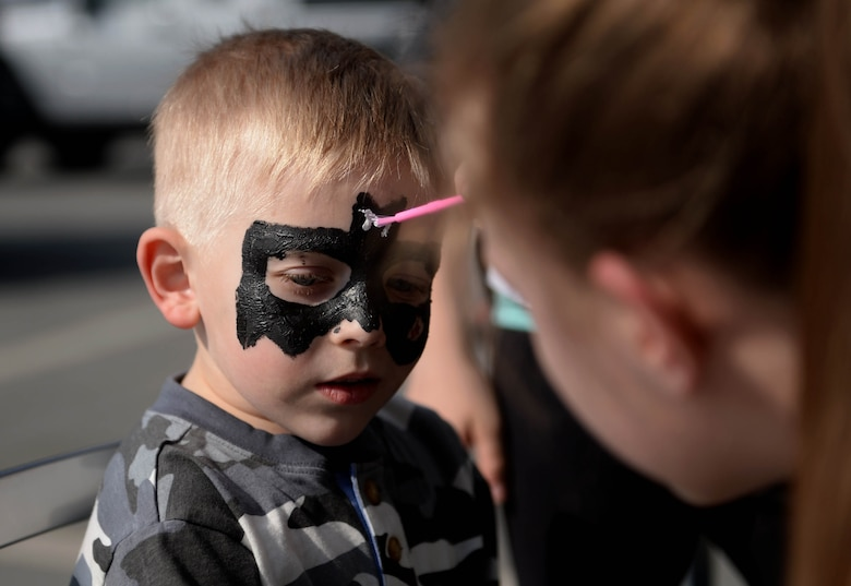 Jacob Stegall, child of Amie Stegall and U.S Air Force Tech Sgt. Robert Stegall, 52nd Logistics Readiness Squadron, receives face paint during the Exceptional Family Member Program Spring Fling at the Base Exchange at Spangdahlem Air Base, March 20, 2015. The Airman & Family Readiness Center hosted the event to raise awareness of the EFMP and the service it provides for families. Members of the base community volunteered to run various activities to ensure family members could experience the fair's full potential. (U.S. Air Force photo by Airman 1st Class Timothy Kim/Released)