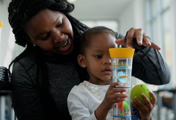 Joy-Nicole Smith, left, and Laurel-Elaine Valerie Smith, right, interact with a sensory activity tool during the Exceptional Family Member Program Spring Fling at the Base Exchange at Spangdahlem Air Base, March 20, 2015. The Airman & Family Readiness Center hosted the event to raise awareness of the EFMP and the service it provides for families. Sensory activities promoted awareness of Exceptional Family Members and educated parents of the resources and activities available to aid them in attending their children's special needs. (U.S. Air Force photo by Airman 1st Class Timothy Kim/Released)