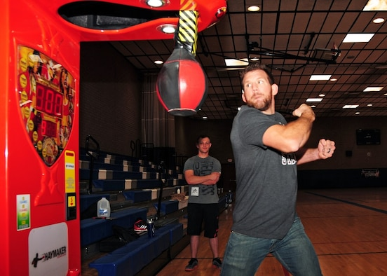 """Ryan """"Darth"""" Bader, Ultimate Fighting Champion fighter, takes a swing at the Haymaker vending machine to measure his punching power Mar 21 during the UFC Fitness Tour 2015 at the Bryant Fitness Center, Luke Air Force Base, Ariz. (U.S. Air Force photo taken by Tech. Sgt. Louis Vega Jr.)"""