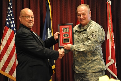 Charles Twing is presented a memento by Col. Robert Ruch, Huntsville Center commander, during Twing's retirement ceremony March 20. Twing served more than 24 years with Huntsville Center and was a pioneer in the Center's ordnance programs.