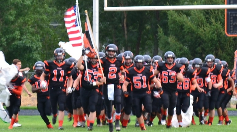 Christen Riedel (#53) carries the American Flag leading the Mountain Home Tigers football team onto the field before a game last season. Christen is finishing his senior year at Mountain Home High School and getting ready to leave for college. (Courtesy Photo)