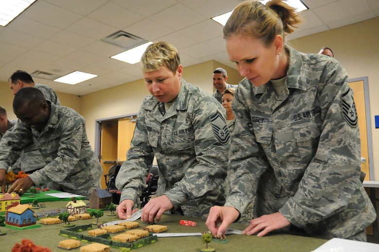 Senior Master Sgt. Shannon Woods and Master Sgt. Aaronnett Bussey, both from the 138th Logistics Readiness Squadron, plot their next move during a table top exercise with during a leadership meeting held Mar. 18, 2015, at the Tulsa Air National Guard Base, Okla.   Since August 2014, every Wednesday following their monthly unit training assembly, leaders from around the 138th Fighter Wing have shared various leadership perspectives, and encouraged open and honest communication while learning from each other at wing leadership meetings .  (U.S. National Guard photo by Senior Master Sgt.  Preston L. Chasteen/Released)