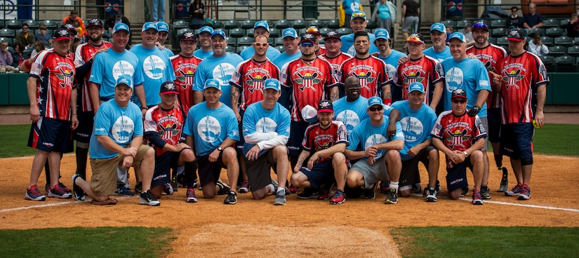 """Members of the Wounded Warrior Amputee Softball Team and The Citadel 1990 College World Series baseball team gather for a group photo March 21, 2015, at Joe Riley Stadium in Charleston, S.C. The """"Battle of Charleston Harbor"""" was a softball game between the Wounded Warrior Amputee Softball Team and The Citadel 1990 College World Series baseball team. (U.S. Air Force photo/Airman 1st Class Clayton Cupit)"""