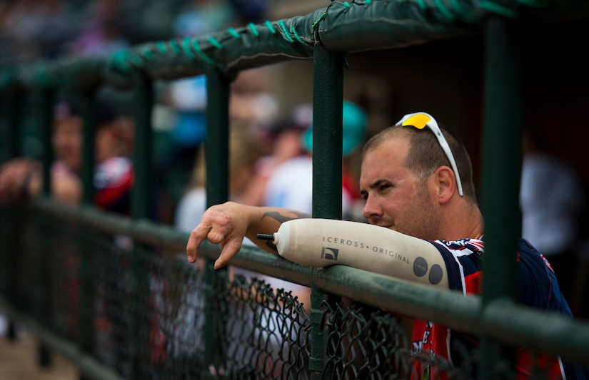 """Leonard Anderson, Wounded Warrior Amputee Softball Team member, watches his teammates play during the """"Battle of Charleston Harbor"""" softball tournament March 21, 2015, at Joe Riley Stadium in Charleston, S.C. The mission of the WWAST is to raise awareness, through exhibition and celebrity softball games, of the sacrifices and resilience of our military and highlight their ability to rise above any challenge. Their goal is to show other amputees and the general public, that these athletes, through extensive rehabilitation and training, are able to express their desires and perform the sport they love. (U.S. Air Force photo/Airman 1st Class Clayton Cupit)"""