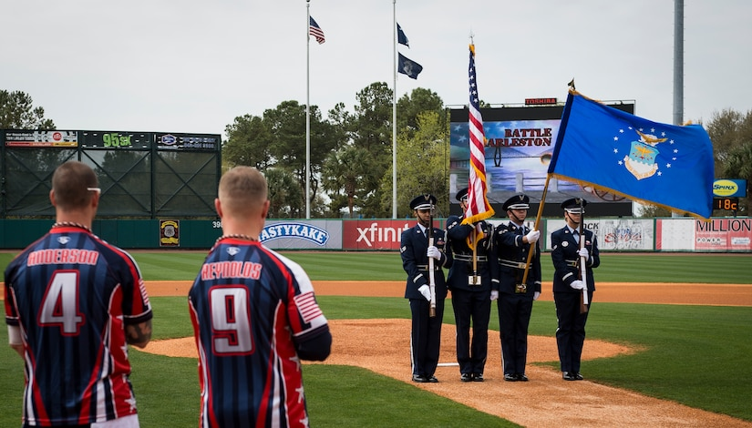 """Joint Base Charleston Honor Guardsmen present the colors while the National Anthem is performed March 21, 2015, at Joe Riley Stadium in Charleston, S.C. The """"Battle of Charleston Harbor"""" was a softball game between the Wounded Warrior Amputee Softball Team and the Citadel 1990 College World Series baseball team. (U.S. Air Force photo/Airman 1st Class Clayton Cupit)"""
