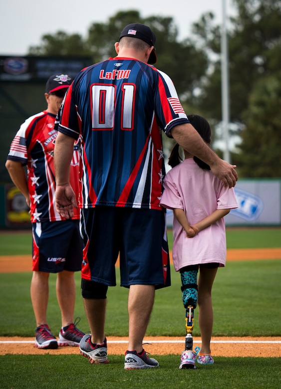 Gary LaFon, Wounded Warrior Amputee Softball Team coach, walks a young girl out on to the field to stand with the WWAST members for the national anthem March 21, 2015, at Joe Riley Stadium in Charleston, S.C. The WWAST is a charitable organization whose mission is to raise awareness, educate and inspire the public about the strength and resiliency of the wounded warriors. The WWAST accomplish their mission by showing how a positive attitude, commitment, dedication and perseverance enable them to overcome any obstacle. (U.S. Air Force photo/Airman 1st Class Clayton Cupit)