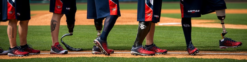 Members of the Wounded Warrior Amputee Softball Team line up on the field  for the playing of the National Anthem March 21, 2015, at Joe Riley Stadium in Charleston, S.C. The WWAST is a charitable organization whose mission is to raise awareness, educate and inspire the public about the strength and resiliency of the wounded warriors.  The WWAST accomplish their mission by showing how a positive attitude, commitment, dedication and perseverance enable them to overcome any obstacle. (U.S. Air Force photo/Airman 1st Class Clayton Cupit)
