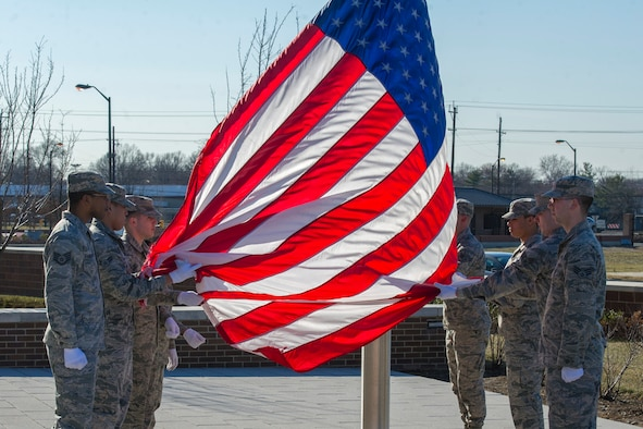 The Joint Base Andrews Honor Guard lowers a U.S. Flag during a retreat ceremony in front of the Jones Building, JBA, Md., March 23, 2015. The flag was retired because its condition was no longer deemed a fitting emblem for display. (U.S. Air Force photo/Airman 1st Class Ryan J. Sonnier)