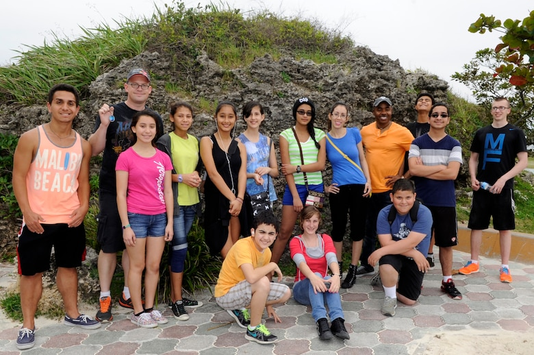 Catholic youth group members from Kadena Air Base, Japan, pose for a photo after finding a geocoin while geocaching near Araha Beach, Japan, March 21, 2015. Geocaching is a new century treasure hunt using GPS and clues provided on a website. Geocoins can occasionally be found in geocaches and are meant to be taken, placed in different caches and tracked around the world. (U.S. Air Force photo by Staff Sgt. Marcus Morris)