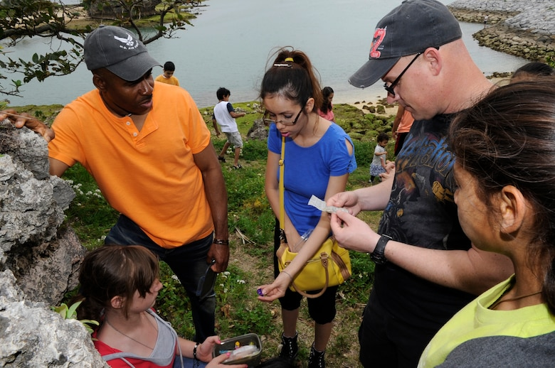 Catholic youth group members from Kadena Air Base, Japan, examine the contents of a geocache near Araha during their monthly outdoor activity, March 21, 2015. Geocaching is like a high-tech treasure hunt using GPS to locate hidden containers. The thrill of the game can be getting to the destination or in actually finding the treasure itself. (U.S. Air Force photo by Staff Sgt. Marcus Morris)