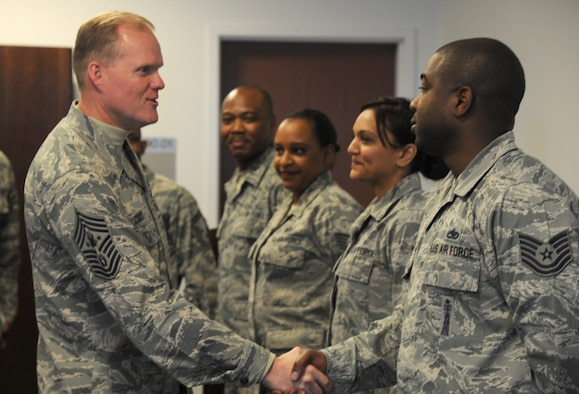 Chief Master Sgt. of the Air Force James A. Cody introduces himself to Tech. Sgt. Thomas White during his visit with Airmen assigned to the Air Force District of Washington March 23, 2015, at Joint Base Andrews, Md. White is the unit training manager for AFDW. (U.S. Air Force photo/Master Sgt. Tammie Moore)