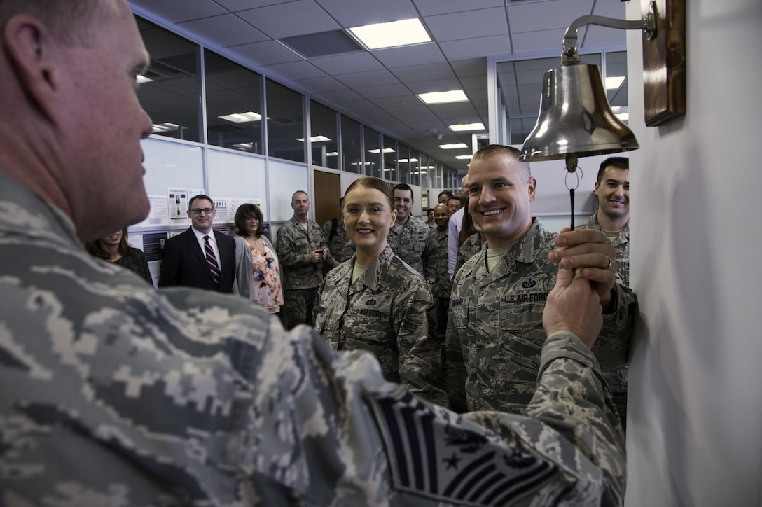 Chief Master Sgt. of the Air Force James Cody rings the victory bell with Airmen from the Air Force Legal Operations Agency March 23, 2015, during his visit to Joint Base Andrews, Md. The bell is rang when there is a legal victory in the office. (U.S. Air Force photo/Airman 1st Class Philip Bryant)