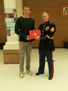 Joe Burrow, the Athens High School quarterback in Athens, Ohio, received a certificate of participation from U.S. Marine Corps Sgt. David A. Wood, a Recruiting Station Charleston recruiter, and native of San Bernardino, California, for playing in the Marine Corps Semper Fidelis Bowl, Jan 4, 2015, at Carson, California. The certificate was presented to Burrow, March 24 in front of the student body in the school cafeteria. (Courtesy photo provided by Sgt. David A. Wood/Released)