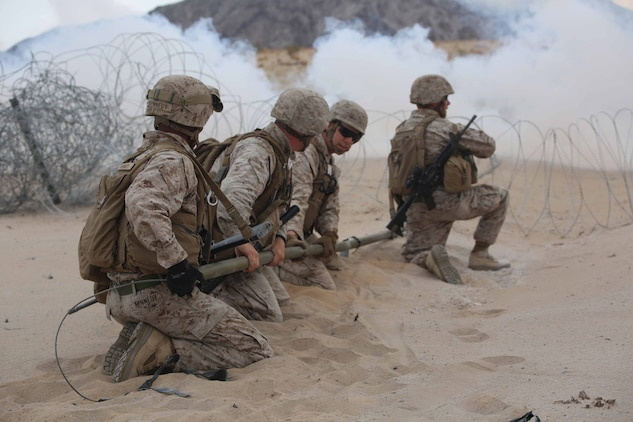 Marines with Engineer Platoon, Headquarters and Service Company, Ground Combat Element Integrated Task Force, snap M1A2 Bangalores together under the concealment of smoke for a hasty breach during a Marine Corps Operational Test and Evaluation Activity assessment at Range 107, Marine Corps Air Ground Combat Center Twentynine Palms, California, March 22, 2015. From October 2014 to July 2015, the GCEITF will conduct individual and collective level skills training in designated ground combat arms occupational specialties in order to facilitate the standards-based assessment of the physical performance of Marines in a simulated operating environment performing specific ground combat arms tasks. (U.S. Marine Corps photo by Cpl. Paul S. Martinez/Released)