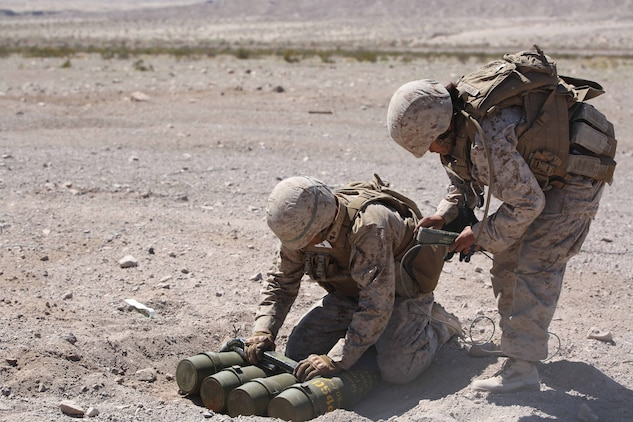 Cpl. Joshua J. Syverson, left, and Cpl. Alicia Hernandez, right, both combat engineers with Engineer Platoon, Headquarters and Service Company, Ground Combat Element Integrated Task Force, prepare C4 charges and detonation cord for cache reduction during a Marine Corps Operational Test and Evaluation Activity assessment at Range 107, Marine Corps Air Ground Combat Center Twentynine Palms, California, March 22, 2015. From October 2014 to July 2015, the GCEITF will conduct individual and collective level skills training in designated ground combat arms occupational specialties in order to facilitate the standards-based assessment of the physical performance of Marines in a simulated operating environment performing specific ground combat arms tasks. (U.S. Marine Corps photo by Cpl. Paul S. Martinez/Released)