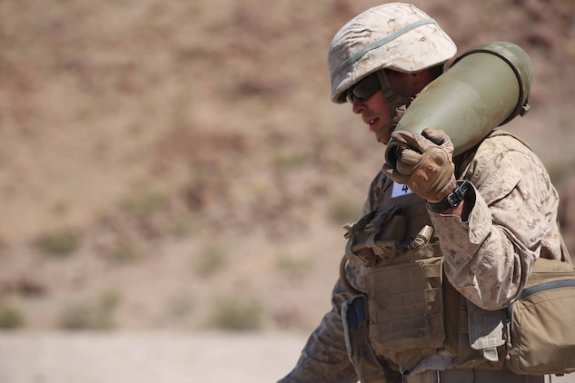 Cpl. Joshua J. Syverson, combat engineer, Engineer Platoon, Headquarters and Service Company, Ground Combat Element Integrated Task Force, carries a 155mm shell during cache reduction as part of a Marine Corps Operational Test and Evaluation Activity assessment at Range 114, Marine Corps Air Ground Combat Center Twentynine Palms, California, March 23, 2015.  From October 2014 to July 2015, the GCEITF will conduct individual and collective level skills training in designated ground combat arms occupational specialties in order to facilitate the standards-based assessment of the physical performance of Marines in a simulated operating environment performing specific ground combat arms tasks. (U.S. Marine Corps photo by Cpl. Paul S. Martinez/Released)