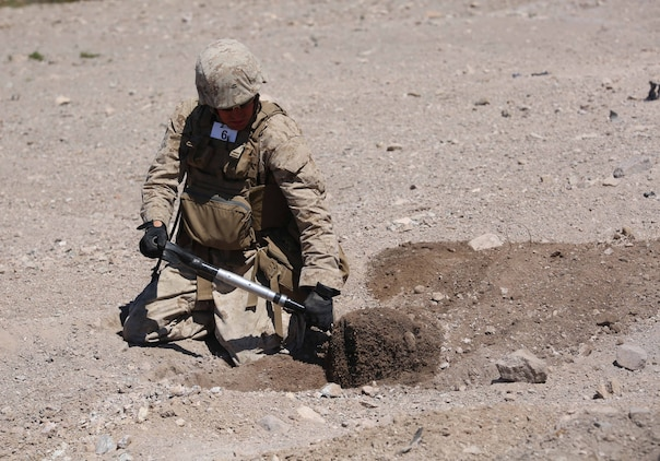 Cpl. Travis Smith, combat engineer, Engineer Platoon, Headquarters and Service Company, Ground Combat Element Integrated Task Force, digs a hole during cache reduction as part of a Marine Corps Operational Test and Evaluation Activity assessment at Range 114, Marine Corps Air Ground Combat Center Twentynine Palms, California, March 23, 2015.  From October 2014 to July 2015, the GCEITF will conduct individual and collective level skills training in designated ground combat arms occupational specialties in order to facilitate the standards-based assessment of the physical performance of Marines in a simulated operating environment performing specific ground combat arms tasks. (U.S. Marine Corps photo by Cpl. Paul S. Martinez/Released)