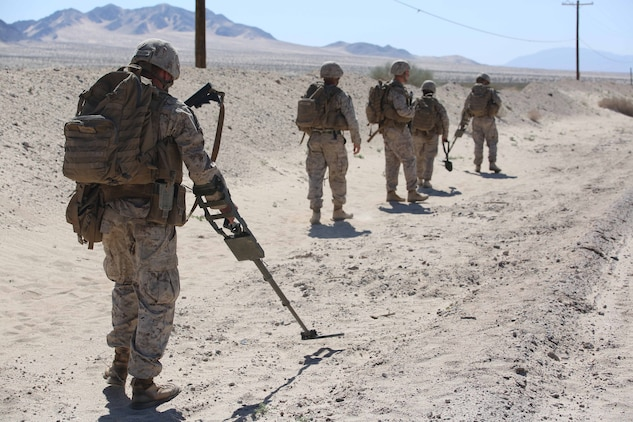 Marines with Engineer Platoon, Headquarters and Service Company, Ground Combat Element Integrated Task Force, sweep for mines during a Marine Corps Operational Test and Evaluation Activity assessment at Range 110, Marine Corps Air Ground Combat Center Twentynine Palms, California, March 23, 2015. From October 2014 to July 2015, the GCEITF will conduct individual and collective level skills training in designated ground combat arms occupational specialties in order to facilitate the standards-based assessment of the physical performance of Marines in a simulated operating environment performing specific ground combat arms tasks. (U.S. Marine Corps photo by Cpl. Paul S. Martinez/Released)