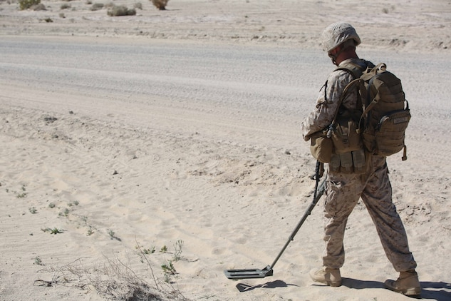 Cpl. Jordan Yearsley, combat engineer, Engineer Platoon, Headquarters and Service Company, Ground Combat Element Integrated Task Force, uses a compact metal detector to sweep for mines during a Marine Corps Operational Test and Evaluation Activity assessment at Range 110, Marine Corps Air Ground Combat Center Twentynine Palms, California, March 23, 2015. From October 2014 to July 2015, the GCEITF will conduct individual and collective level skills training in designated ground combat arms occupational specialties in order to facilitate the standards-based assessment of the physical performance of Marines in a simulated operating environment performing specific ground combat arms tasks. (U.S. Marine Corps photo by Cpl. Paul S. Martinez/Released)
