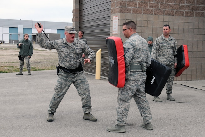 Master Sgt. Mitchell Hooper demonstrates baton techniques to members of the 
