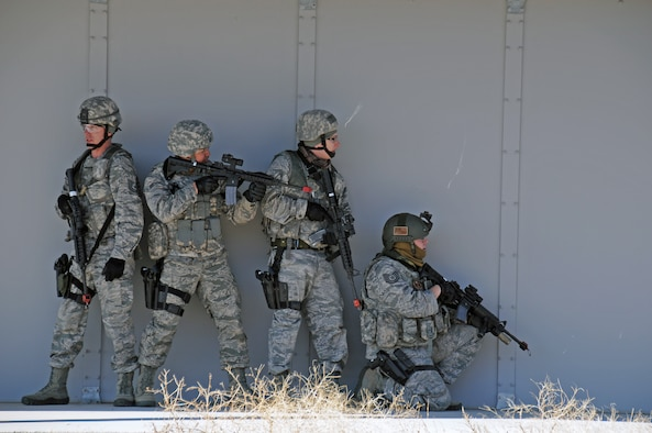 From left: Tech. Sgt. Casy Carsten, Airman 1st Class Adam Cazimero, Senior  Airman Samuel Gudmundson, and Tech. Sgt. Nicholas Nelson, members of the 151st  Security Forces Squadron, participate in a simulated assault on a village at  the Military Operations in Urban Terrain Range at Camp Williams, Utah, on  March 9, 2015. (Air National Guard photo by Staff Sgt. Annie Edwards/RELEASED)