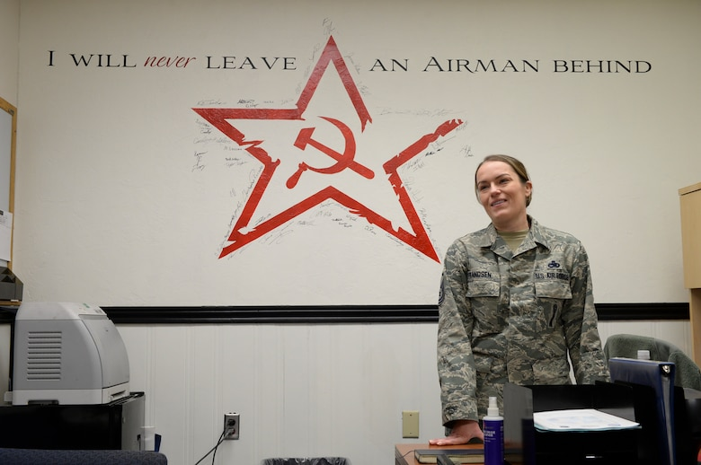 U.S. Air Force Master Sgt. Keri Frandson, the 354th Aircraft Maintenance Squadron armament flight chief, discusses artwork she commissioned to one of her prior Airmen in the F-16 Fighting Falcon fighter aircraft hangars March 18, 2015, Eielson Air Force Base, Alaska. Frandsen visited members of her previous shop. (U.S. Air Force photo by Senior Airman Peter Reft/Released)