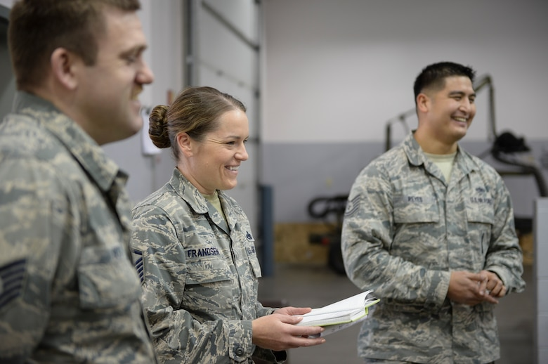 U.S. Air Force Master Sgt. Keri Frandson, the 354th Aircraft Maintenance Squadron armament flight chief, leads a morning all call with Tech. Sgt. Neal Beck, the armament maintenance non-commissioned officer in charge, and Tech. Sgt. Victor Reyes, the armament support NCOIC, at the armament back shop March 18, 2015, Eielson Air Force Base, Alaska. Frandsen took accountability for each shop section and updated Airmen with news and reports. (U.S. Air Force photo by Senior Airman Peter Reft/Released)