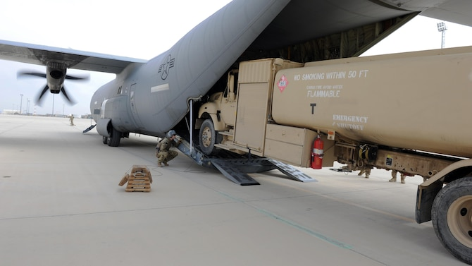 U.S. Air Force Lt. Col. Thomas Lankford, 774th Expeditionary Airlift Squadron commander, acts as a spotter as an R-11 fuel truck is loaded onto a C-130J Super Hercules aircraft during a redeployment mission at an undisclosed location in the Air Force Central Command area of responsibility March 15, 2015. The ability to forward deploy mission critical equipment, such as the R-11, to key sites throughout the AOR is more imperative than ever before as the Air Force reduces its footprint in the region. (U.S. Air Force photo by Staff Sgt. Whitney Amstutz)