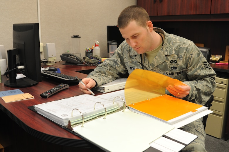 Staff Sgt. Andy Moore, 319th Air Base Wing Command Post NCO-in-charge of C2 systems, goes over training records in th CP Training office on Grand Forks Air Force Base, N.D., March 24, 2015. Moore was selected as the Warrior of the Week for the fourth week of March 2015. (U.S. Air Force photo by Staff Sgt. David Dobrydney/Released)