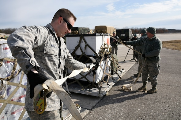 Senior Airman Daniel Mage, 127th Logistics Readiness Squadron aerial port specialist, uses a tie-down strap to secure equipment to a pallet on the flight line at the Alpena Combat Readiness Training Center, Mich., March 20, 2015. The 127th LRS is supporting a Michigan Army National Guard exercise. It took the 127th LRS team less than 48 hours to prepare and load more than 80 tons of equipment and approximately 100 soldiers onto the three aircraft. (U.S. Air National Guard photo by Senior Airman Ryan Zeski/Released)
