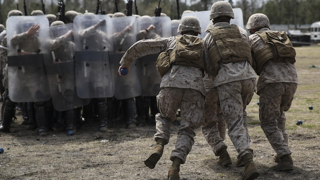 Marines with Battery and Golf Co., 2nd Battalion, 6th Marines, acting as role-players, rush into a blockade of Marines as part of a riot control exercise aboard Camp Lejeune, N.C., March 24, 2015. The role-players attempted to break the wall of shields, testing the effectiveness of their shield, baton and movement techniques while in formation.
