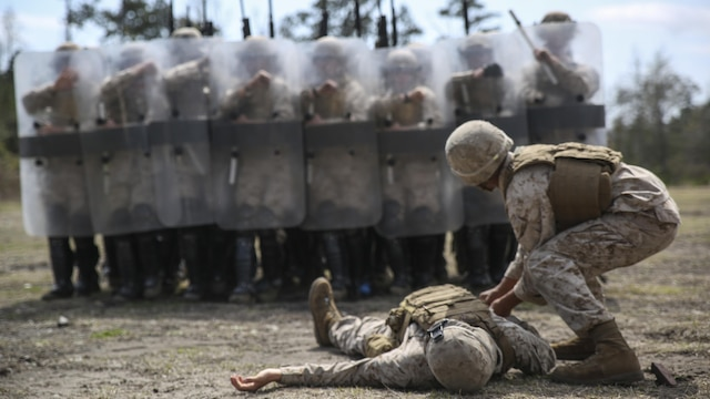 "Marines with Battery and Golf Co., 2nd Battalion, 6th Marines, acting as role-players, stand guard around a mock casualty during a riot control exercise aboard Camp Lejeune, N.C., March 24, 2015. Staff Sgt. Shawn J. Dyer, the lead non-lethal weapons instructor with Expeditionary Operations Training Group, II MEF, said, ""You have to work in unison, moving together in step with the shields and firing the weapons."""
